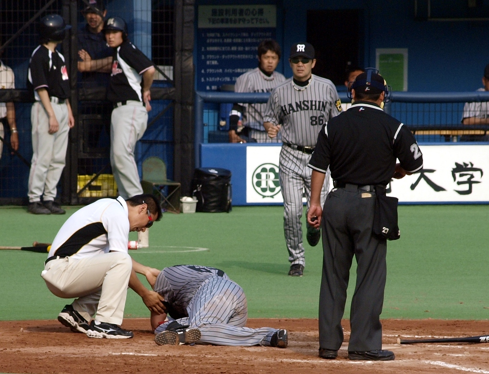 Hanshin staff checks out an injured Brazell